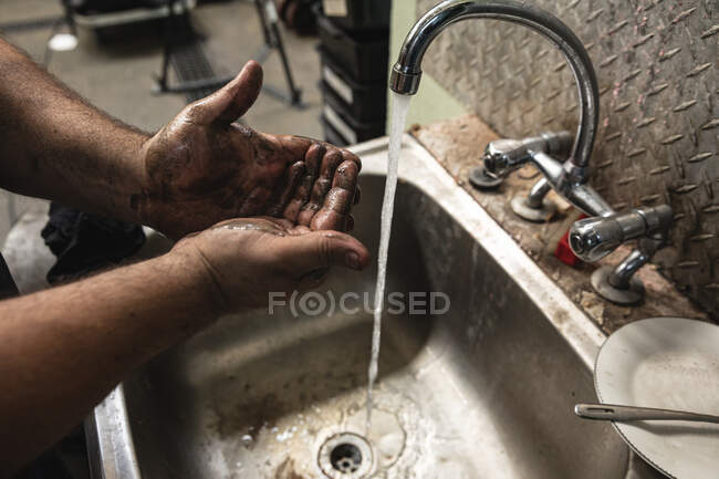 Close up of male factory worker standing at a sink and washing dirty hands. — Stock Photo