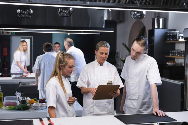 Caucasian female chef holding a file of papers, talking to Caucasian male and female chefs, standing by her with other chefs standing in the background. — Stock Photo