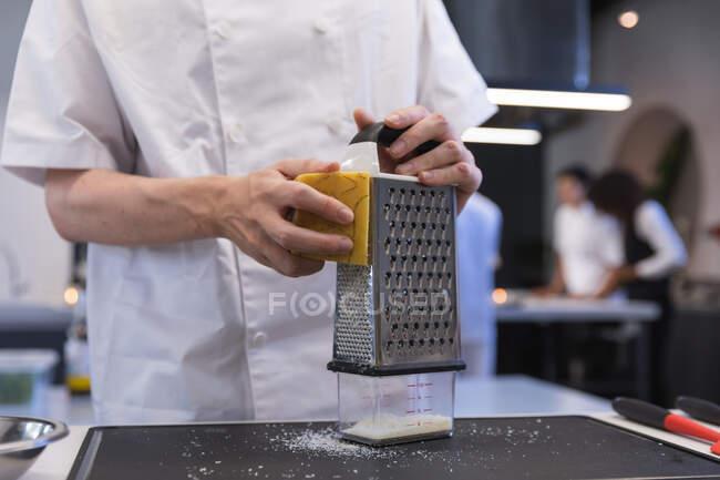 Vista de mitad de la sección de chef hembra rallando queso duro en un rallador. - foto de stock