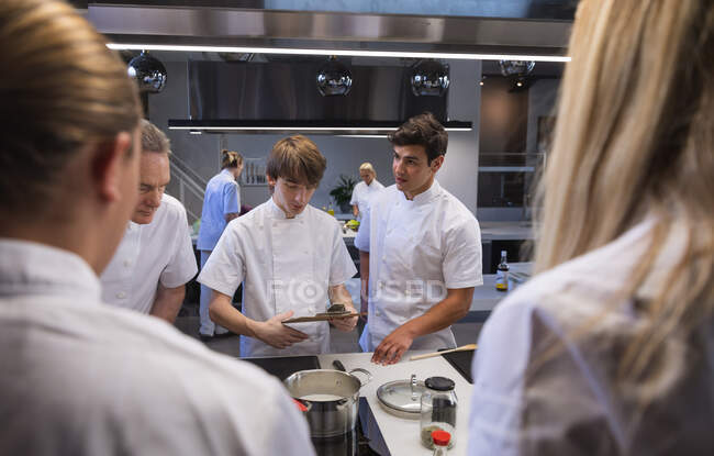 Three Caucasian male chefs standing by a table, looking at pans and pots, talking to each other, with Caucasian female chefs in the foreground. Cookery class at a restaurant kitchen. — Stock Photo