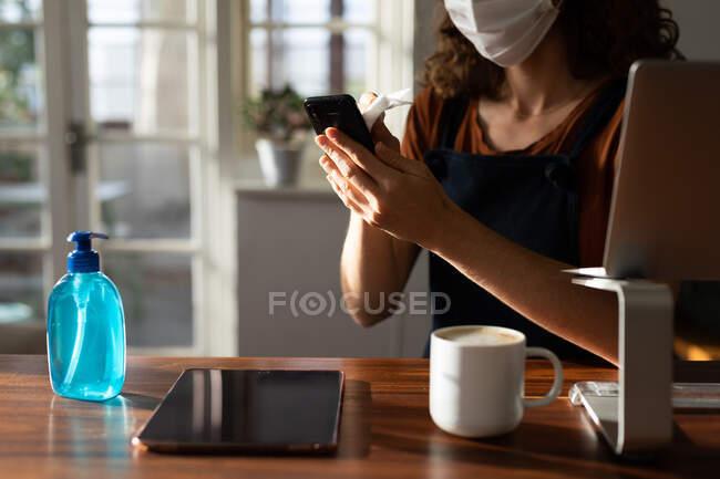 Eine Kaukasierin, die Zeit zu Hause verbringt, von zu Hause aus arbeitet, ihr Smartphone benutzt und eine Gesichtsmaske trägt. Lebensstil zu Hause Isolation in Quarantäne Lockdown während Coronavirus covid 19 Pandemie. — Stockfoto