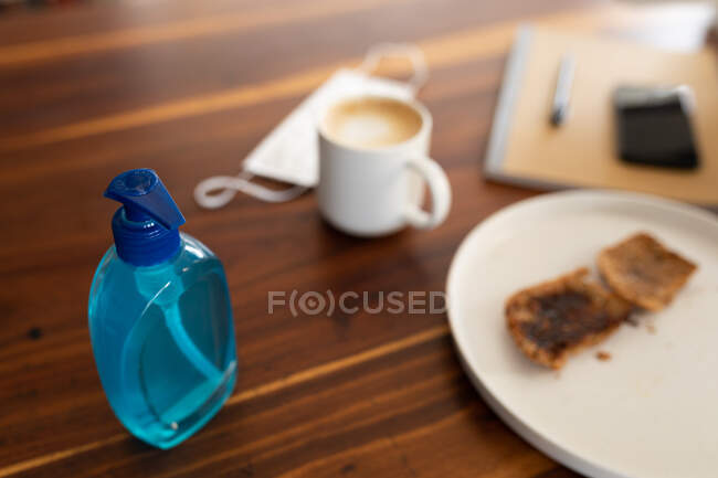 Закрыть маску для лица, антисептик для рук, кружку с кофе и еду на деревянном столе. Стиль жизни дома изолирует, социальное дистанцирование в карантинной изоляции во время пандемии коронавируса ковид 19. — стоковое фото
