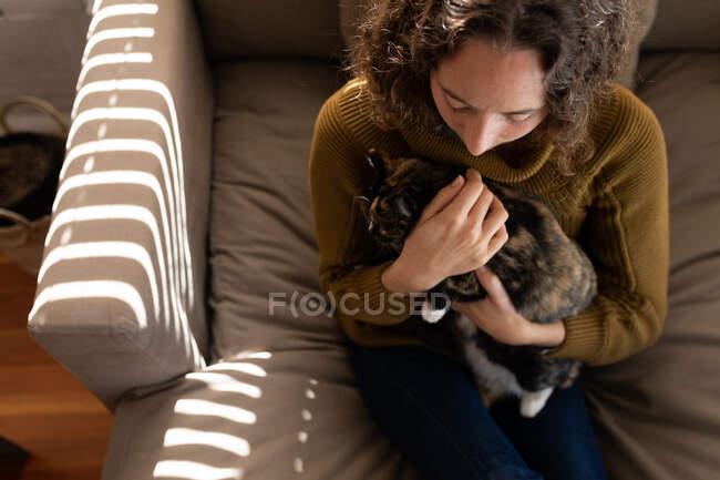 Una mujer caucásica pasando tiempo en casa, sentada en el coche, sosteniendo a su gato. Estilo de vida en el hogar aislamiento, distanciamiento social en cuarentena bloqueo durante coronavirus covid 19 pandemia. - foto de stock