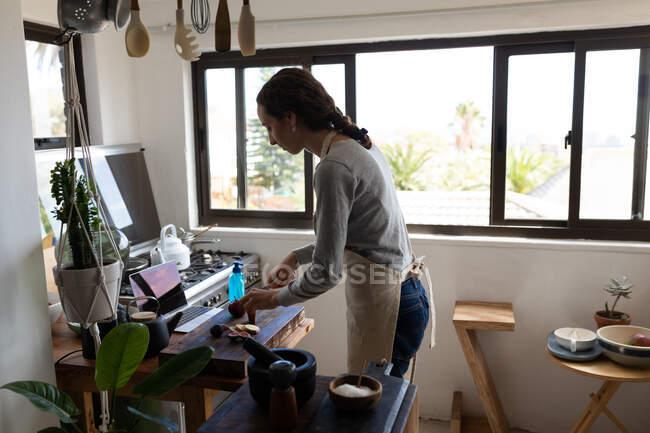 Una mujer caucásica que pasa tiempo en casa, preparando comida en la cocina. Estilo de vida en el hogar aislamiento, distanciamiento social en cuarentena bloqueo durante coronavirus covid 19 pandemia. - foto de stock