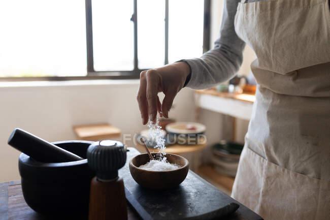 Sección media de la mujer que pasa tiempo en casa, preparando comida, usando sal. Estilo de vida en el hogar aislamiento, distanciamiento social en cuarentena bloqueo durante coronavirus covid 19 pandemia. - foto de stock