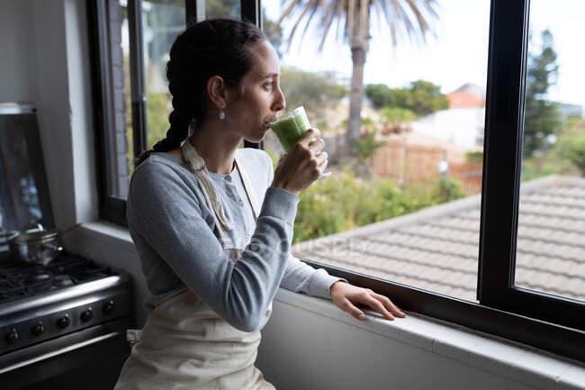 Una mujer caucásica pasando tiempo en casa, bebiendo batido. Estilo de vida en el hogar aislamiento, distanciamiento social en cuarentena bloqueo durante coronavirus covid 19 pandemia. - foto de stock