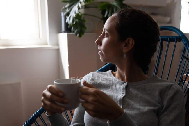 Una mujer caucásica pasando tiempo en casa, bebiendo café. Estilo de vida en el hogar aislamiento, distanciamiento social en cuarentena bloqueo durante coronavirus covid 19 pandemia. - foto de stock