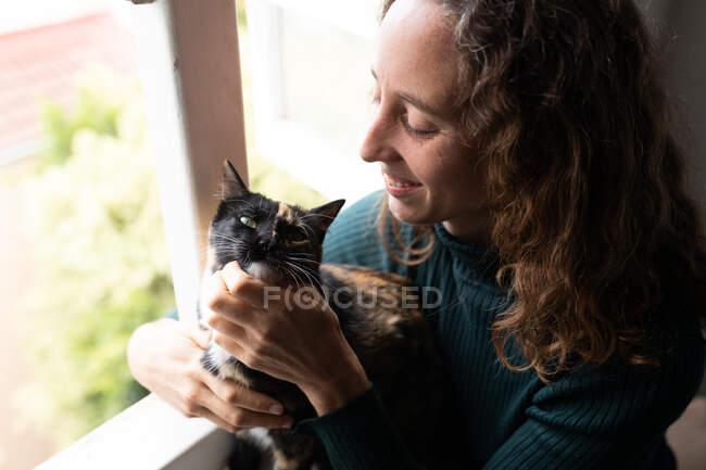 Una mujer caucásica pasando tiempo en casa acariciando a su gato. Estilo de vida en el hogar aislamiento, distanciamiento social en cuarentena bloqueo durante coronavirus covid 19 pandemia. - foto de stock