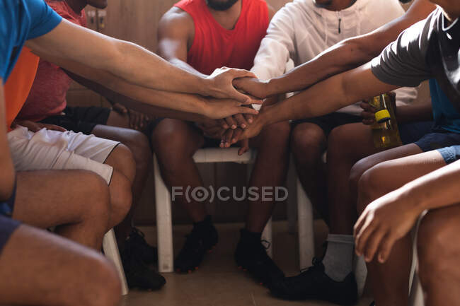 Low section of group of male football players wearing sports clothes sitting in changing room during a break in game, hand stacking and motivating each other. — Stock Photo