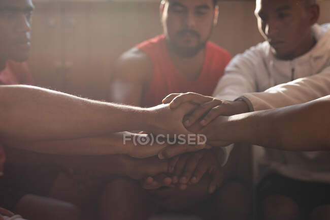 Multi ethnic group of male football players wearing sports clothes sitting in changing room during a break in game, hand stacking and motivating each other. — Stock Photo