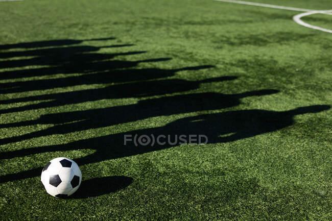Тіні на траві групи гравців чоловічої футбольної команди тренуються на спортивному полі на сонці, стоячи поруч один з одним м'ячем.. — стокове фото