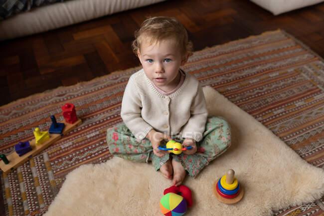 Bebê menina brincando e olhando para a câmera, ela está olhando para cima e sorrindo na sala de estar de sua casa. — Fotografia de Stock