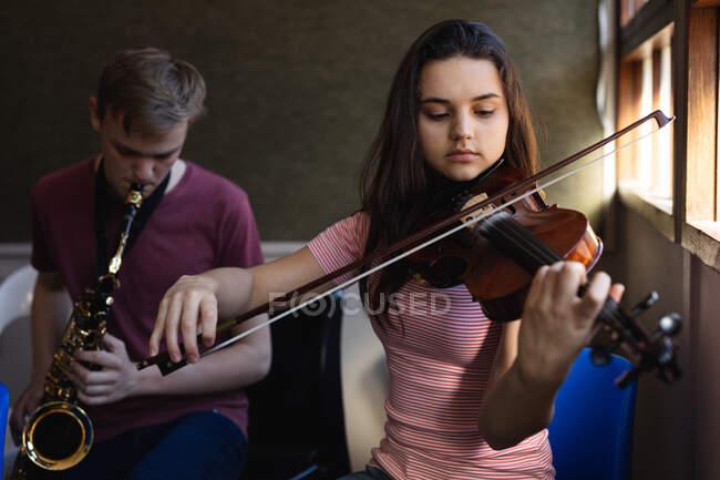 Vue de face d'un adolescent caucasien musicien masculin et féminin répétant, la fille jouant du violon et le garçon jouant du saxophone — Photo de stock