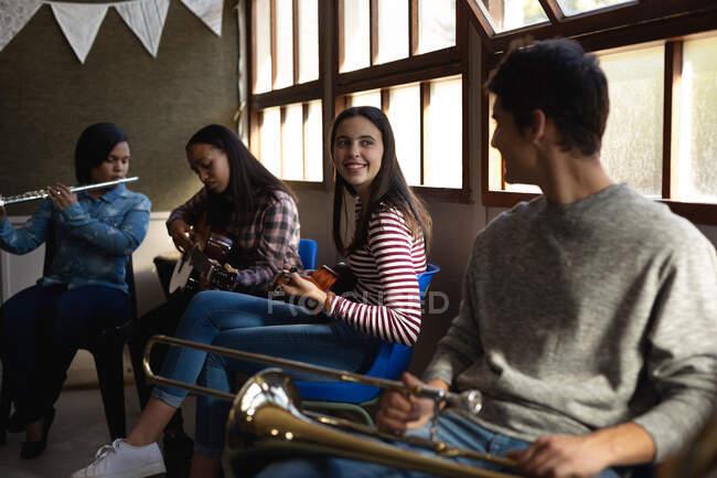Vue latérale d'un groupe multi-ethnique de musiciens adolescents, hommes et femmes, assis dans une salle de classe, discutant pendant une pause dans la pratique de leur orchestre scolaire — Photo de stock
