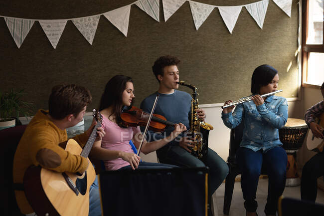 Vue de face d'un groupe multi-ethnique de musiciens adolescents, hommes et femmes, assis dans une salle de classe, jouant de leurs instruments lors d'une répétition d'une fanfare scolaire — Photo de stock