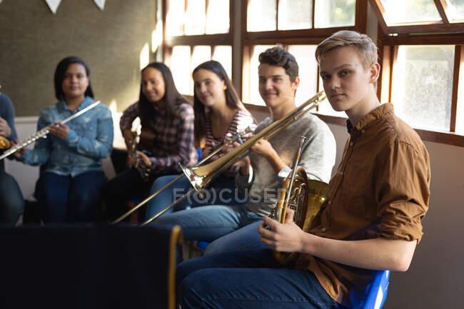 Vue latérale d'un adolescent blanc tenant assis devant une fenêtre dans une salle de classe tenant un cor français avec un groupe multi-ethnique d'adolescents musiciens masculins et féminins assis derrière lui — Photo de stock