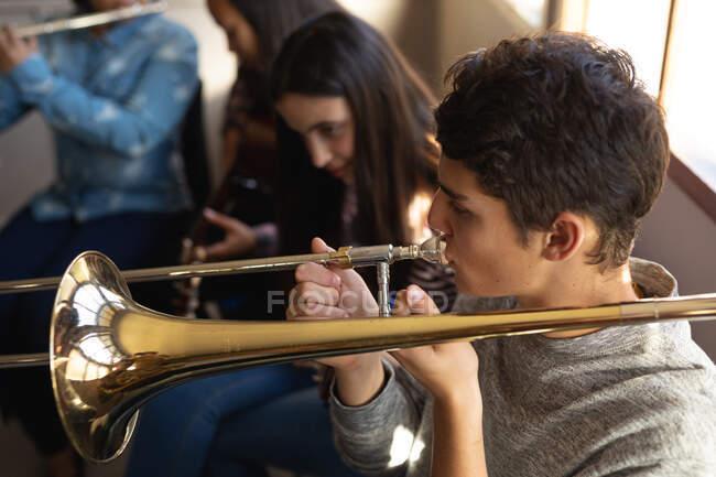 Vue en angle élevé d'un adolescent caucasien jouant du trombone lors d'une pratique d'un groupe scolaire, avec une adolescente caucasienne et d'autres musiciens adolescents assis en arrière-plan — Photo de stock