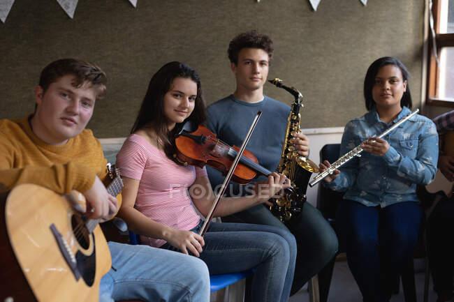 Vue de face d'un groupe multi-ethnique de musiciens adolescents, hommes et femmes, assis dans une salle de classe tenant leurs instruments pendant une pause à l'école. — Photo de stock