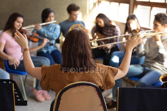 Vue arrière d'une femme caucasienne assise et dirigeant un groupe multiethnique de musiciens adolescents masculins et féminins jouant dans un groupe scolaire — Photo de stock