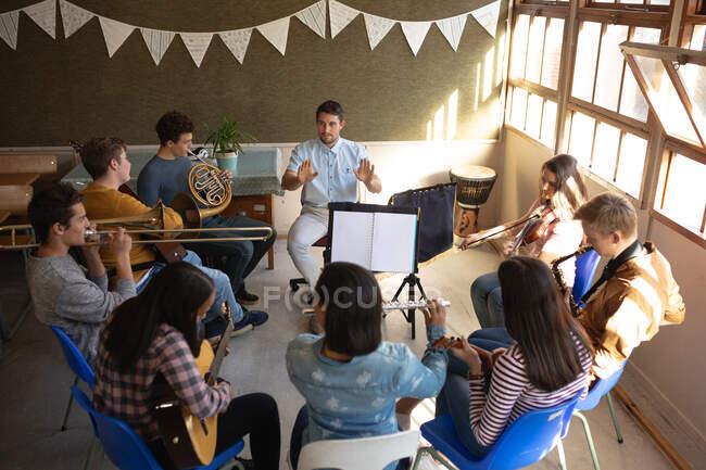 Vue de face en grand angle d'un enseignant caucasien assis dans une salle de classe conduisant un groupe multi-ethnique de musiciens adolescents masculins et féminins dans une pratique de la fanfare scolaire — Photo de stock