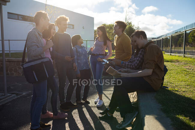 Side view of a multi-ethnic group of male and female teenagers hanging out smiling laughing and talking in their school grounds in the sunlight — Stock Photo
