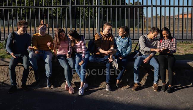 Вид спереди на многоэтническую группу студентов мужского и женского пола, сидящих на стене, разговаривающих и пользующихся планшетными компьютерами на территории школы — стоковое фото