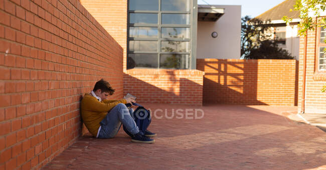 Side view of a sad lonely bullied Caucasian isolated teenage boy sitting on the ground alone in a schoolyard reading — Stock Photo