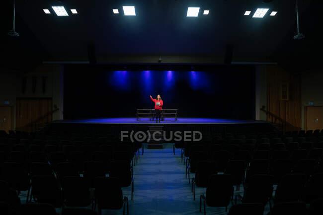Frontansicht eines Teenagers mit gemischter Rasse, der während der Proben für eine Aufführung in einem leeren Schultheater auf der Bühne steht und ein Drehbuch hält — Stockfoto