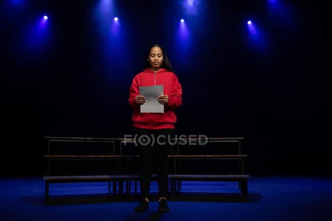 Вид спереди на девочку-подростка смешанной расы, стоящую на сцене с сценарием в пустом школьном театре во время репетиций спектакля — стоковое фото