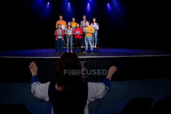 Задний план кавказской женщины-дирижера, руководившей многоэтнической группой юношей и девушек-хористов, держащих ноты и поющих стоя на сцене школьного театра во время репетиций спектакля — стоковое фото