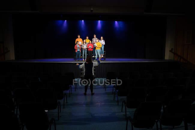 Rückansicht einer kaukasischen Dirigentin, die eine multiethnische Gruppe von jugendlichen Sängerinnen und Sängern dirigiert, die Noten in der Hand halten und während der Proben für eine Aufführung auf der Bühne eines Schultheaters singen — Stockfoto