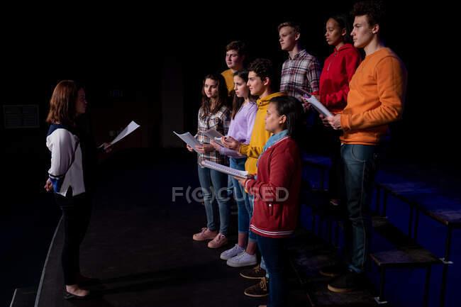 Vista laterale di una regista caucasica e di un gruppo multietnico di coristi adolescenti maschili e femminili in piedi uno di fronte all'altro che tengono spartiti e cantano sul palco di un teatro scolastico durante le prove per uno spettacolo — Foto stock