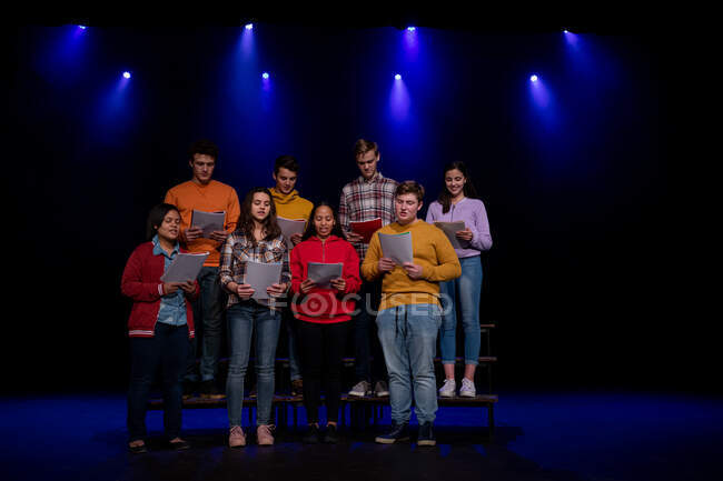 Front view of a multi-ethnic group of teenage male and female choristers holding sheet music and singing standing on the stage of a school theatre during rehearsals for a performance — Stock Photo