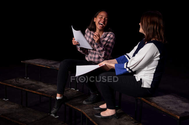 Side view of a Caucasian and a mixed race teenage girls holding scripts and laughing, sitting on the stage of a school theatre during rehearsals for a performance — Stock Photo
