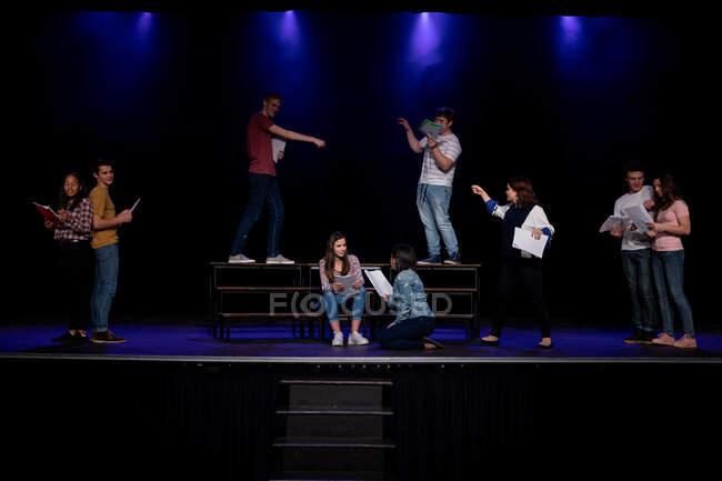 Обзор мультиэтнической группы мальчиков и девочек, держащих сценарии и выступающих на сцене школьного театра во время репетиций спектакля — стоковое фото