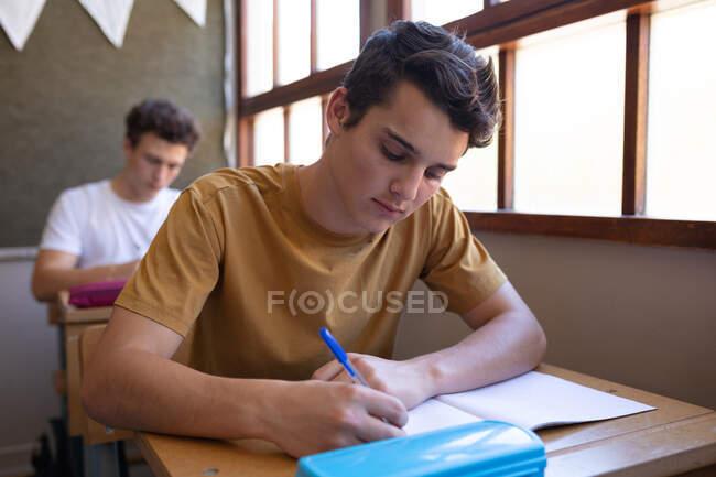 Vista frontal de perto de um adolescente caucasiano sentado em uma mesa em uma sala de aula da escola escrevendo em um caderno, com um colega sentado em uma mesa no fundo — Fotografia de Stock
