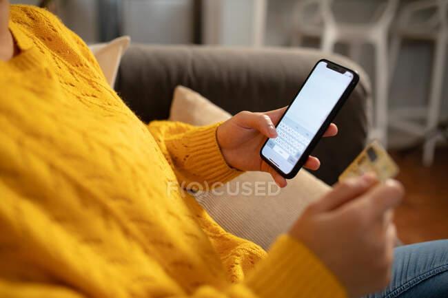 Vue latérale partie médiane de la femme se relaxant à la maison, assis sur un canapé, tenant une carte de crédit et utilisant son smartphone pour faire un achat en ligne — Photo de stock