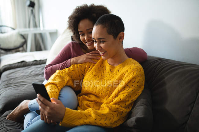 Боковой вид смешанной расы женская пара расслабляется дома, сидя на диване обнимаясь, улыбаясь и глядя на смартфон — стоковое фото
