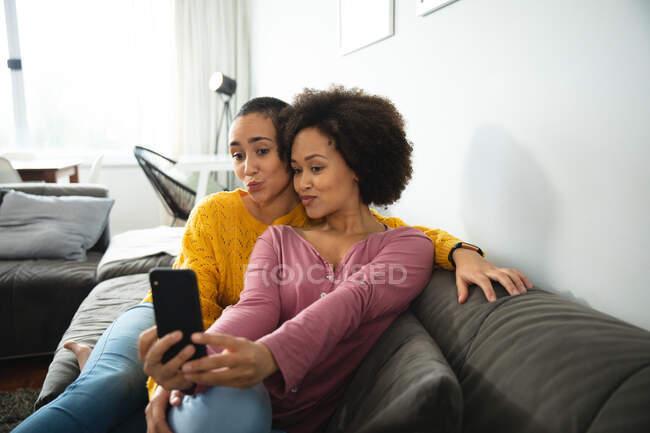 Передний вид смешанной расы женская пара расслабляется дома сидя на диване вместе, один из них держит смартфон и оба позируют для селфи — стоковое фото