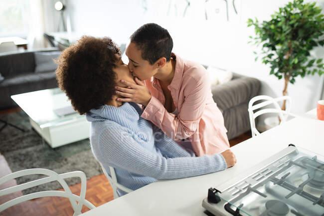 Передній вигляд змішаної раси Жіноча пара відпочиває вдома, обіймаючи і цілуючи пристрасно на кухні сидячи на кухонному острові — стокове фото