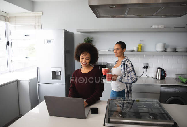Front view of mixed race female couple relaxing at home, standing in the kitchen one woman using a laptop computer while the other carries two cups of coffee, both smiling — Stock Photo