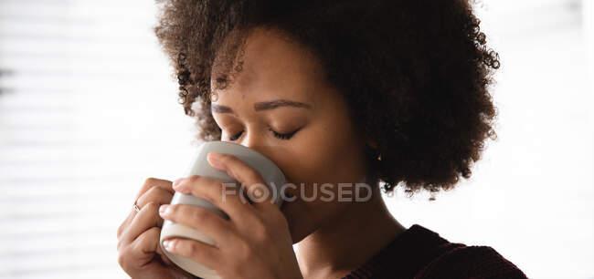 Vista frontal de cerca de la mujer mestiza relajándose en casa, disfrutando bebiendo una taza de café, sosteniéndolo con ambas manos, con los ojos cerrados - foto de stock