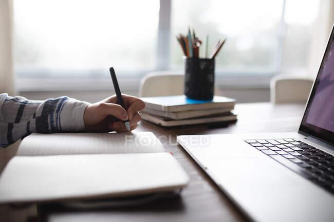 Рука і рука жінки сидять за столом і пишуть у записнику з ноутбуком на столі на передньому плані. — стокове фото