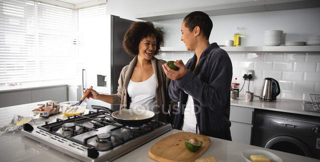 Front view of mixed race female couple relaxing at home, standing in the kitchen preparing breakfast together and laughing. They are beating eggs and holding an avocado — Stock Photo