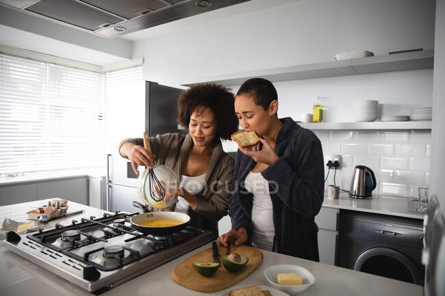 Front view of mixed race female couple relaxing at home, standing in the kitchen making breakfast together, talking and eating — Stock Photo