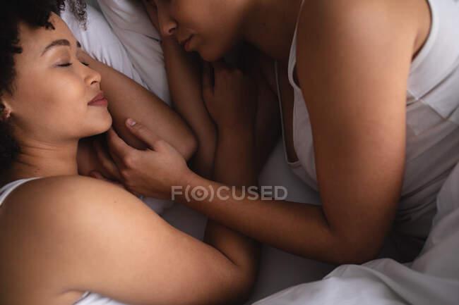 Alto angolo vista da vicino di una coppia di donne di razza mista a casa in camera da letto, sdraiato addormentato a letto insieme al mattino, di fronte all'altro — Foto stock