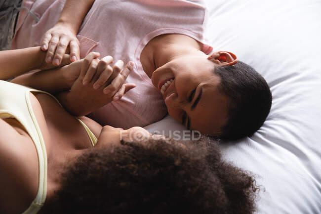 Vista lateral vista de cerca de una pareja femenina de raza mixta relajándose en casa en el dormitorio juntos por la mañana, acostados en la cama en su ropa de dormir, tomados de la mano y mirándose sonriendo - foto de stock