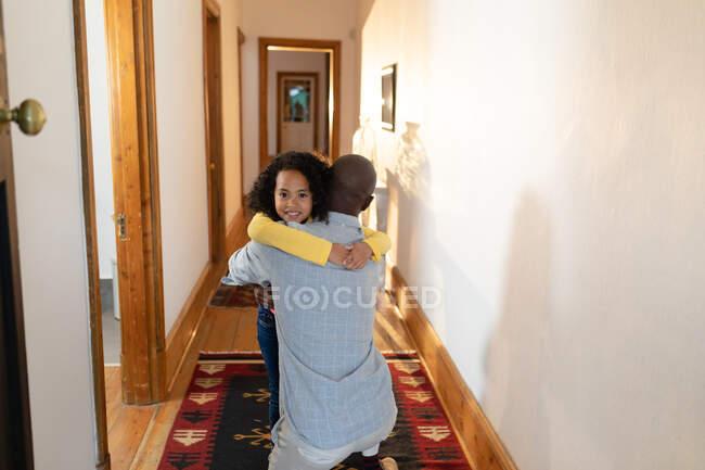 Vista frontal de una joven afroamericana abrazando a su padre mientras se arrodilla en el pasillo de su casa, y sonriendo sobre su hombro - foto de stock