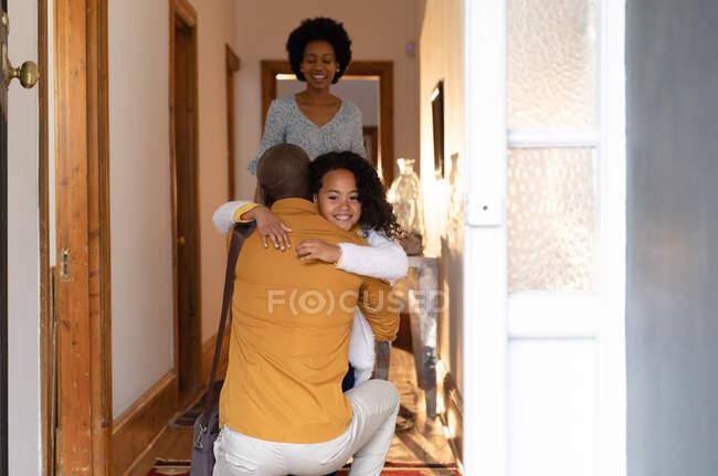 Vista frontal de una joven afroamericana abrazando a su padre mientras se arrodilla en el pasillo en casa, y sonriendo sobre su hombro, con su madre de pie detrás de su sonrisa - foto de stock
