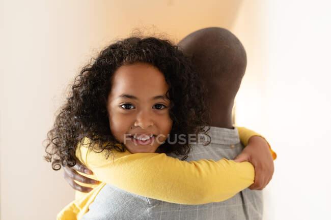 Vista frontal de cerca de una joven afroamericana con el pelo rizado largo abrazando a su padre mientras la sostiene en el pasillo en casa, y sonriendo sobre su hombro - foto de stock